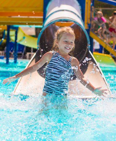 Kid on water slide at aquapark at summer holiday